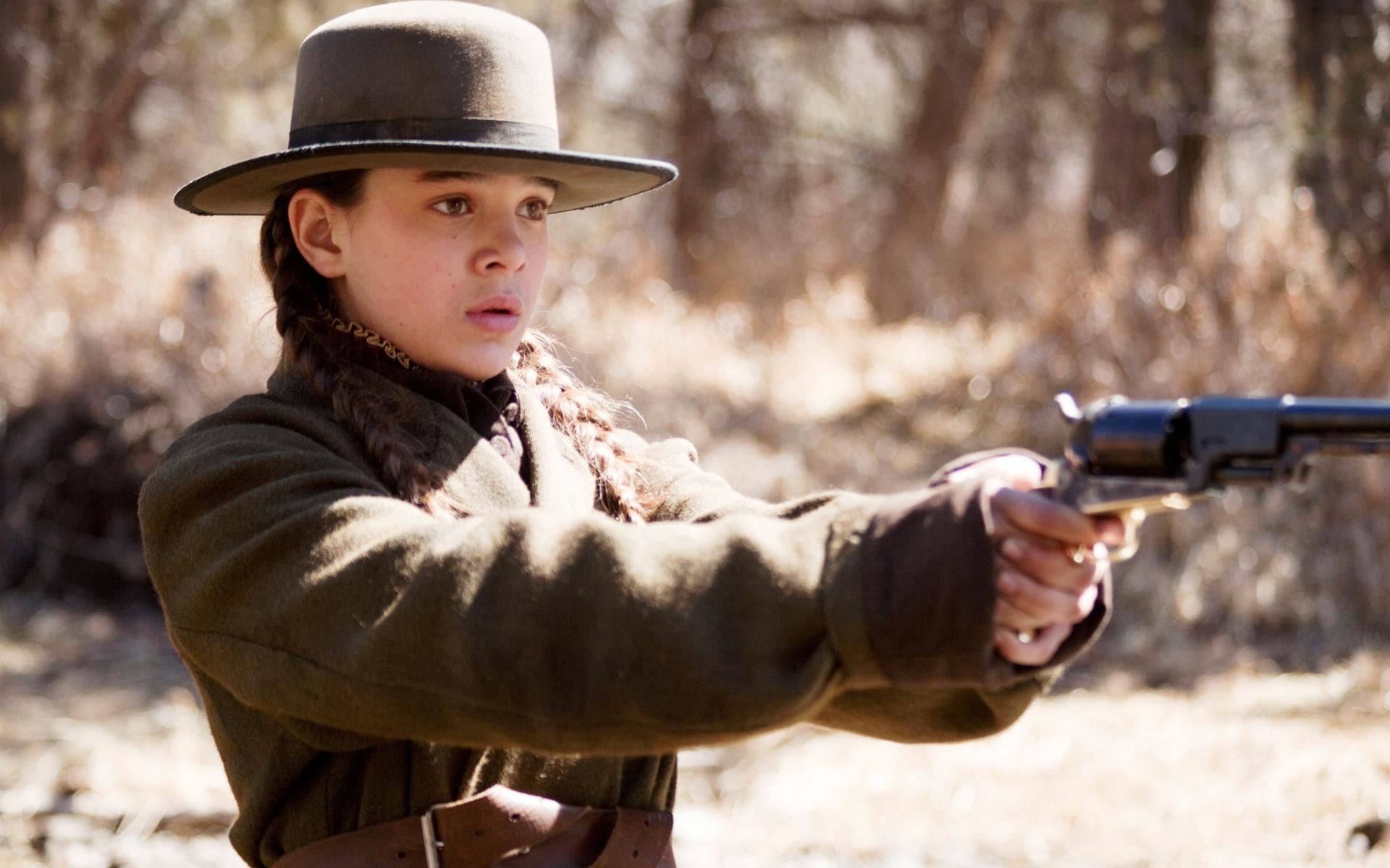 A atriz, vestida com jaqueta marrom e chapéu de abas largas e retas da mesma cor, segura uma arma com as duas mãos e a aponta pra frente. O cenário é desértico.