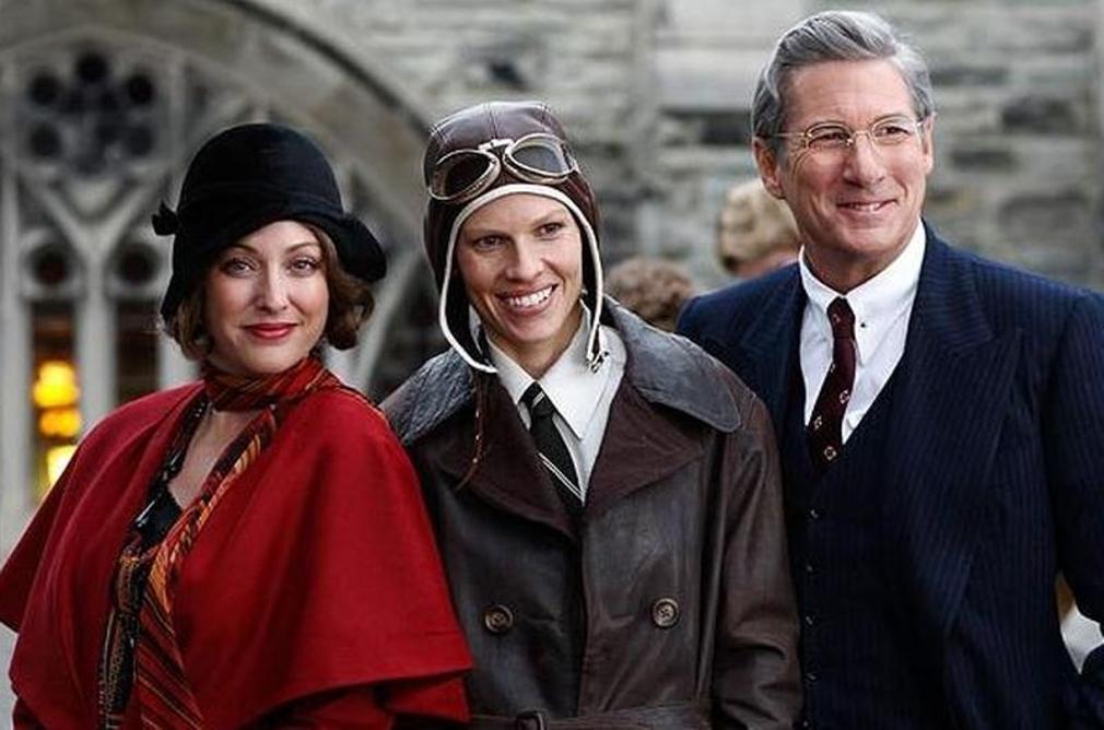 Na foto, uma mulher de roupa vermelha e um homem de paletó azul marinho ladeiam Hilary Swank, atriz que interpreta Amelia, que veste uma jaqueta de couro marrom e uma touca de piloto.