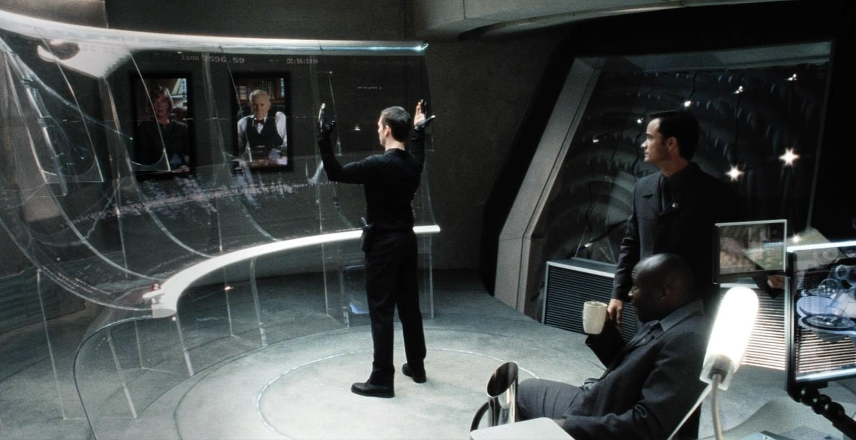 Tom Cruise, vestido inteiramente de preto, gesticula em frente a uma tela curva e transparente, observado por outros dois homens.