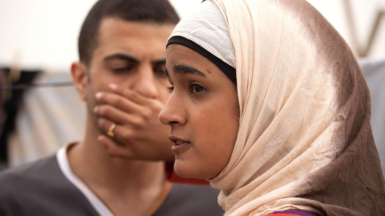 Uma jovem de hijab rosa clarinho e camiseta de manga longa rosa pink, cobre a boca de um rapaz que a observa com sua mão.