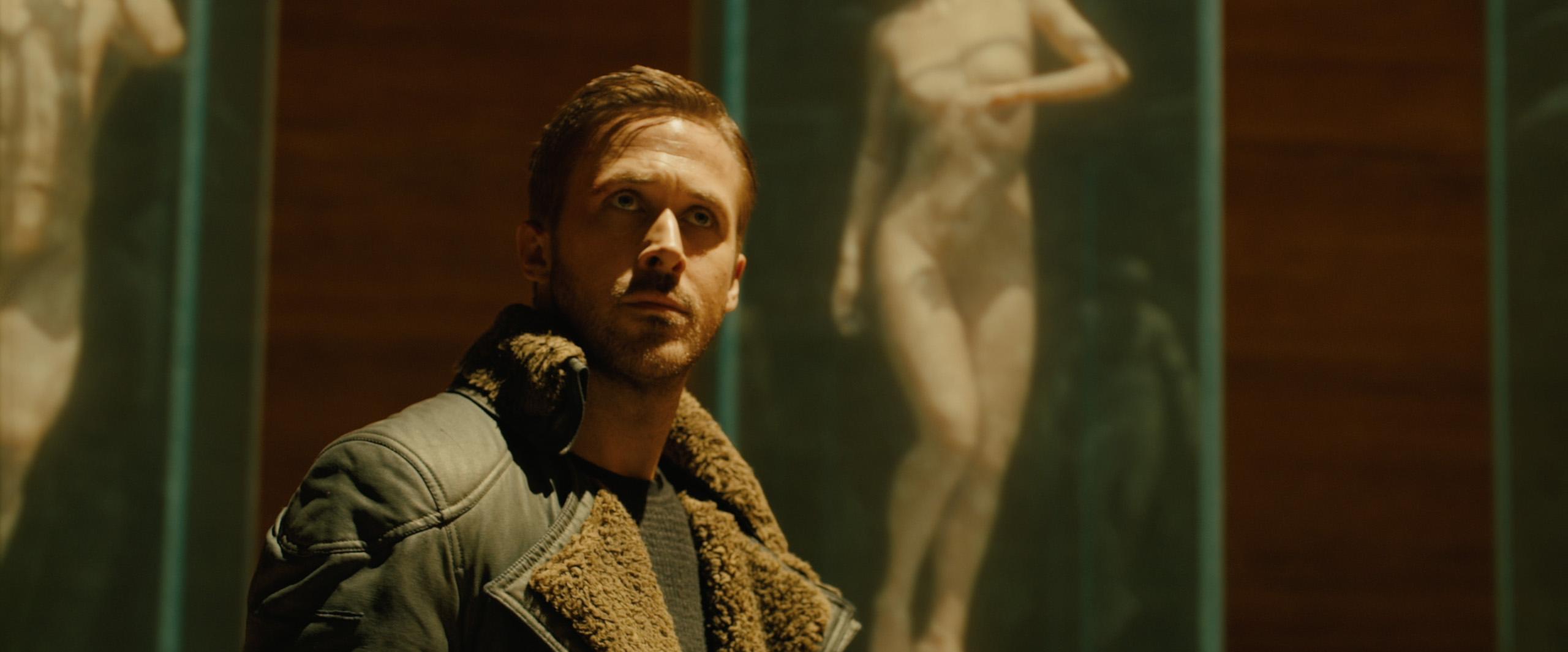Ryan Gosling, vestindo uma jaqueta verde com lapela larga de pele falsa de carneiro. Atrás dele uma espécie de aquário mostra um corpo feminino nu sendo gerado.