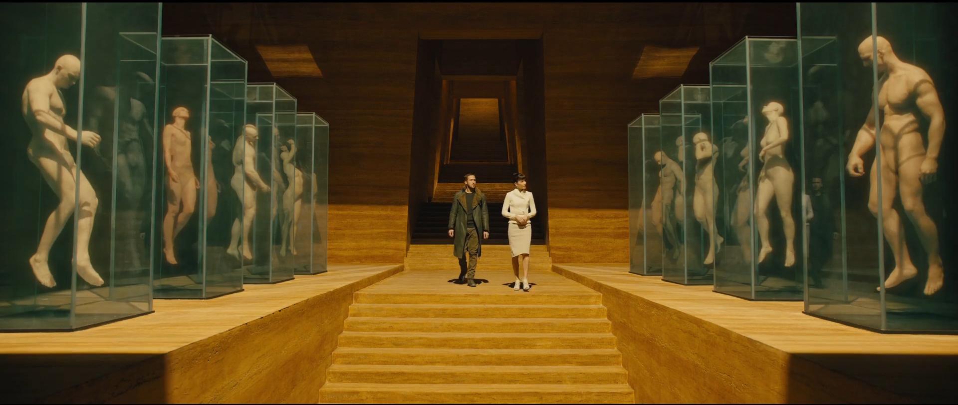 Rya Gosling e Sylvia Hoeks (Luv) caminha em direção a uma escada em um grande salão rodeado por aquários contendo corpos humanos