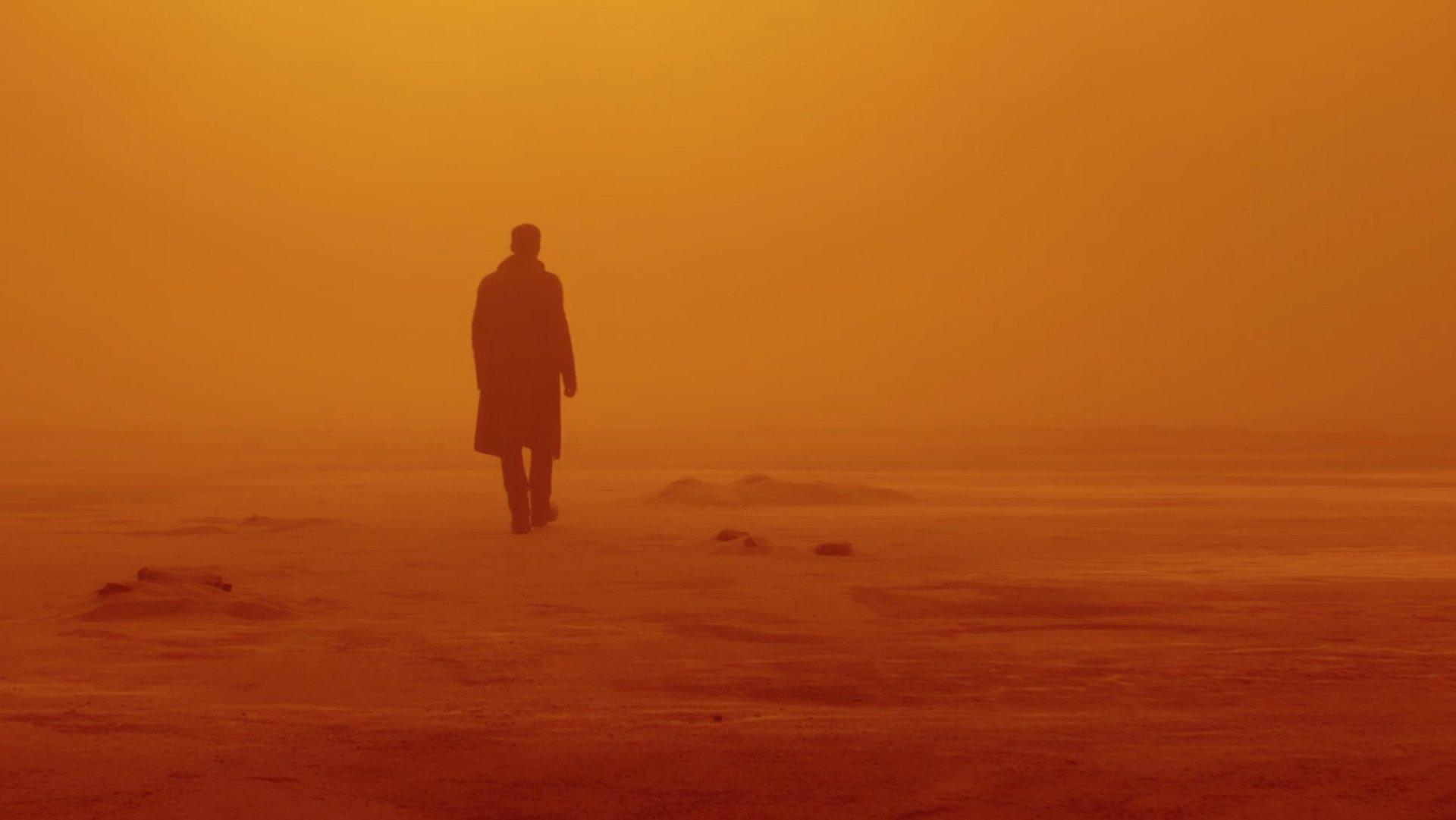 A silhueta de Ryan Gosling, em marrom, se distanciando de quem a olha enquanto se embrenha em um deserto com chão, céu e névoa amarelos