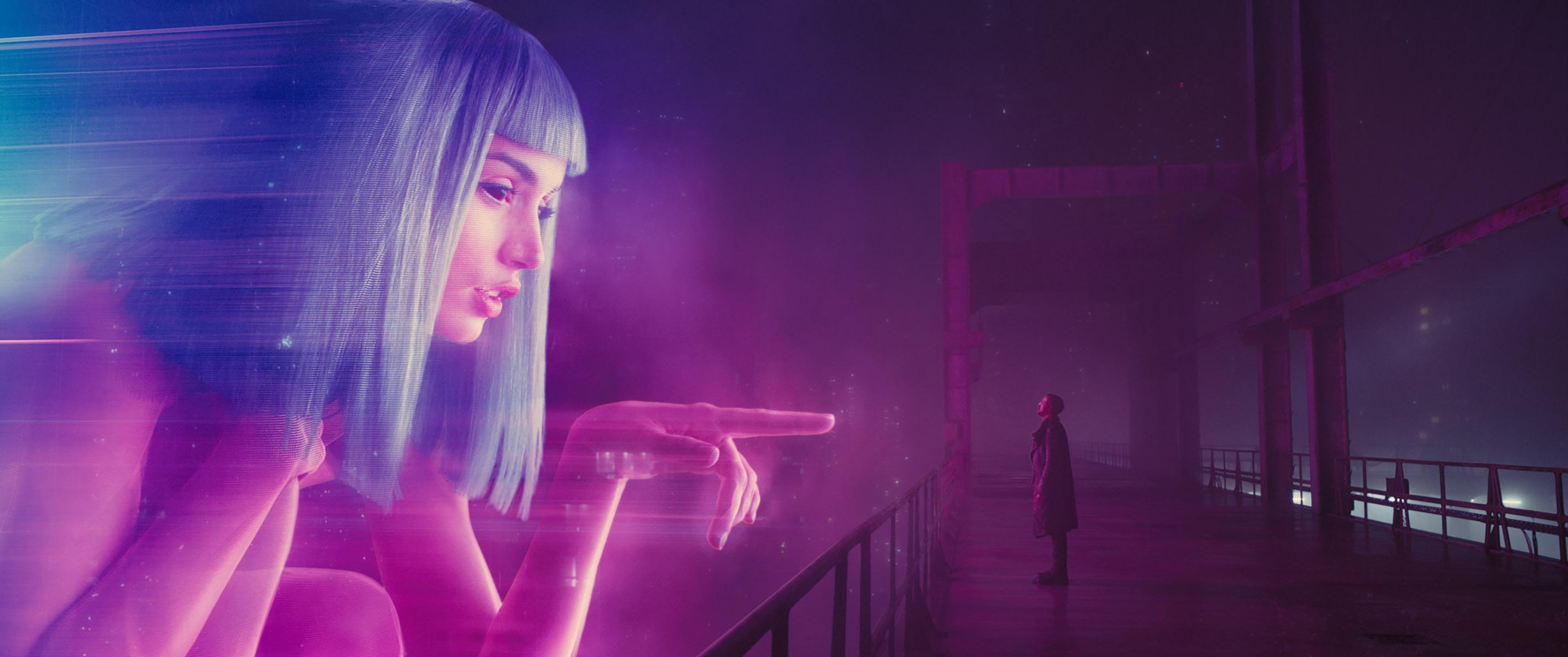 À distância, vemos Ryan |Gosling pequeno em uma ponte e um holograma de mulher com cabelos roxos gigante a sua frente. Ela aponta para ela e a ponta do seu dedo é do tamanho de sua cabeça.