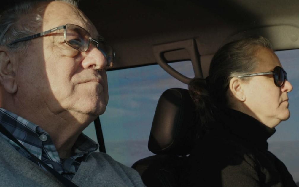 Dentro de um carro, Heloisa Passos, a diretora, dirigindo, e seu pais sentado no banco de passageiro