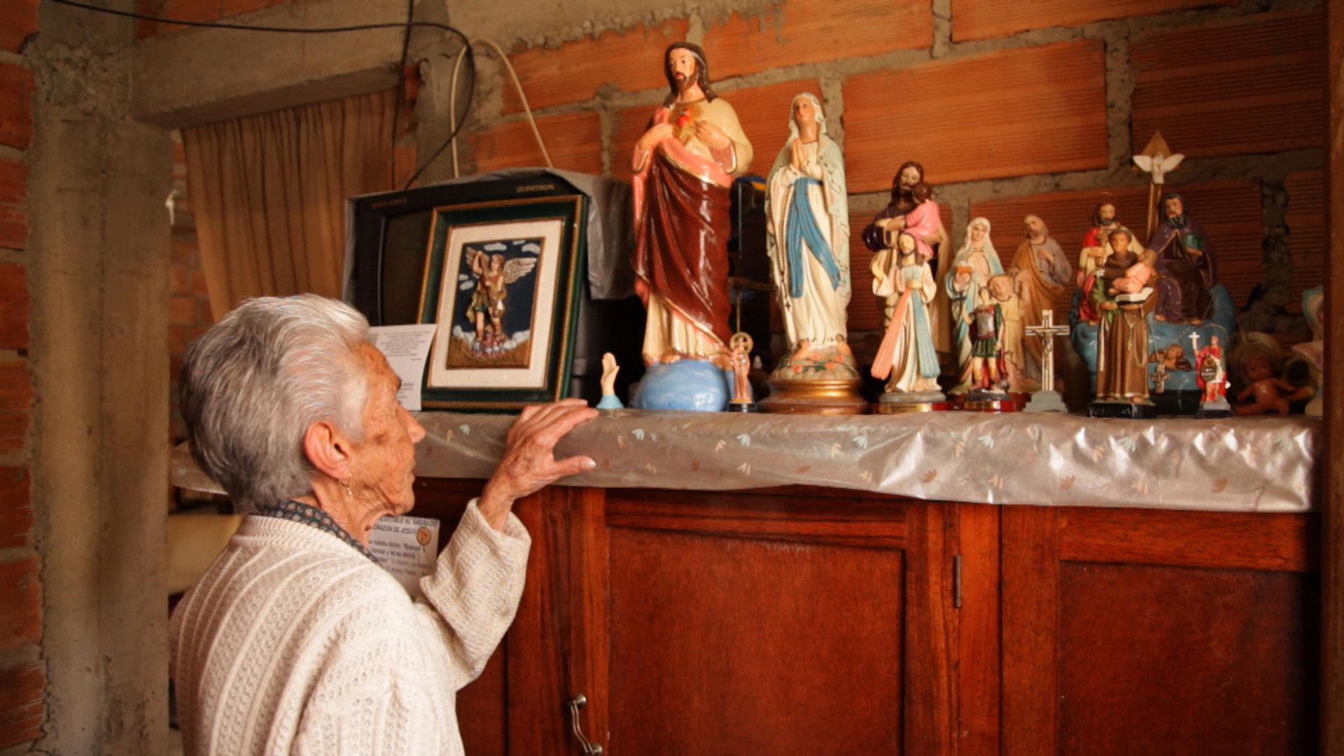 Uma senhora de costas, com cabelos brancos, olha para uma coleção de esculturas de santos perfiladas sobre um armário
