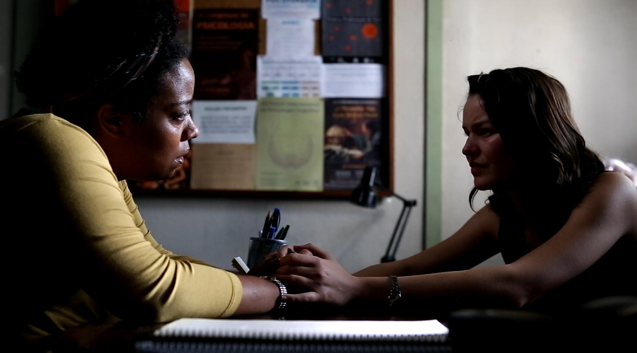 Sentadas uma de frente para a outra estão Glória à esquerda e Camila à direita. Há uma mesa entre as duas, que esticam os braços e unem as suas mãos.