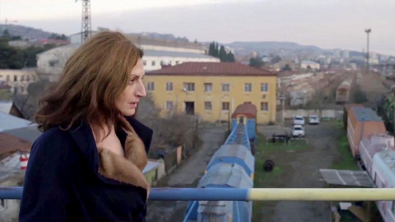 Com ar preocupado, uma mulher com cabelo solto e bagunçado caminha por uma espécie de ponte. Só é visível o corrimão, mas é possível ver as construções abaixo.