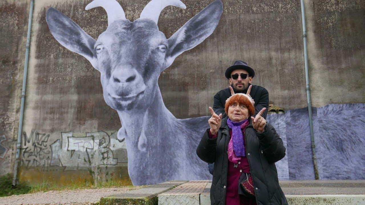 Um grande muro com uma foto gigante de um cabra colada sobre ele. Na sua frente, Agnès Varda e JR, diretores do filmes, fazem chifrinhos com os dedos