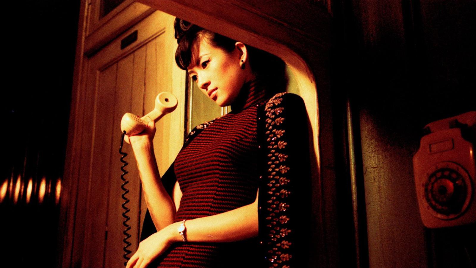 A atriz Zhang Ziyi, de 2016, apoiada com as costas em uma parede segurando um telefone na mão enquanto olha o chão. usa um vestido justo e listrado em tons escuros, um casaco preto sobre os ombros e um relógio de pulso pequeno com pulseira fina no pulso esquerdo.